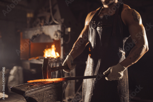 Fotografija muscular forger man with beard using hammer for beating iron manufacture at smit
