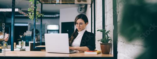 Slika na platnu Young woman using laptop in loft cafe