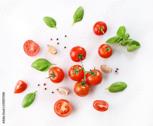 Photographie Ripe red cherry tomatos  and basil on white background. Top view