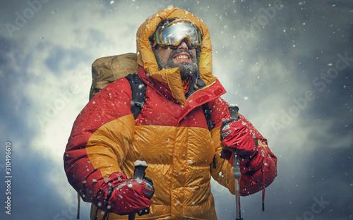Fotografie, Tablou Climber reaching the summit. Snow storm.