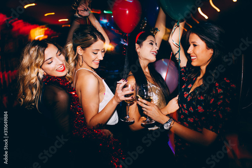 Female friends drinking wine and celebrating new year at the club Fototapeta