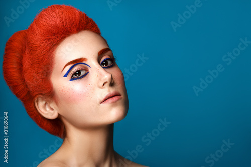Stampa su Tela Beautiful girl with colored in red hair and blue eyeliner makeup isolated on blu