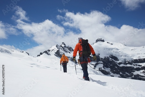 Hikers Joined By Safety Line In Snowy Mountains Fototapeta