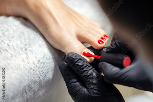 Hands in black gloves are doing red pedicure or manicure on woman's toes, close up.