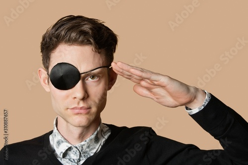 Fotografie, Obraz Portrait of a man wearing eye patch saluting over colored background