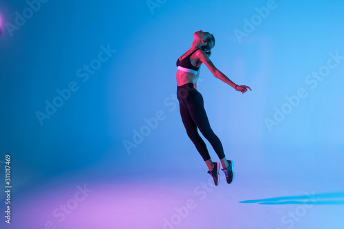 Fototapeta Sporty young woman fitness jumping isolated on purple light background