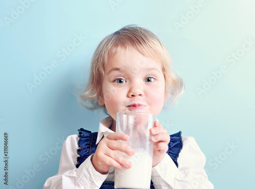 Stampa su Tela Child girl with glass of milk on blue background