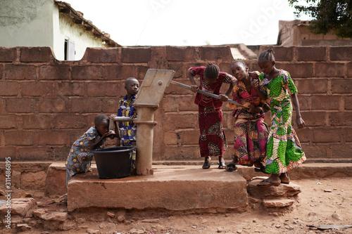 Fotografia African Children Fetching Drinking Water At Their Modern Village Water Pump