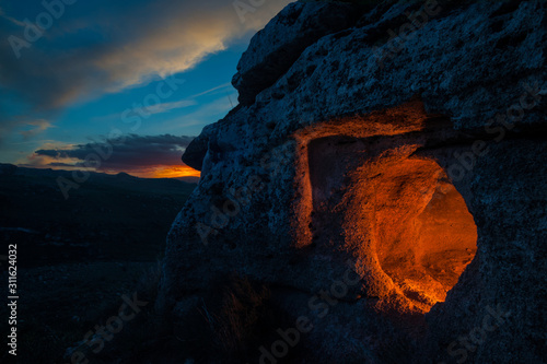 Obraz na płótnie Grotto by night: view of an enlightened rocky tomb at dusk, Pantalica necropolis
