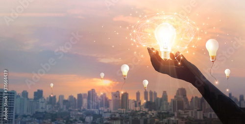 Hand holding light bulb and brain and network connection on city background, Idea and imagination, Creative and inspiration. Innovation future and technology.