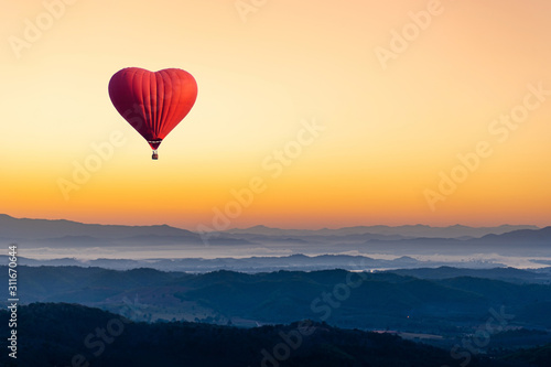 Red hot air balloon in the shape of a heart flying over the mountain Fototapeta