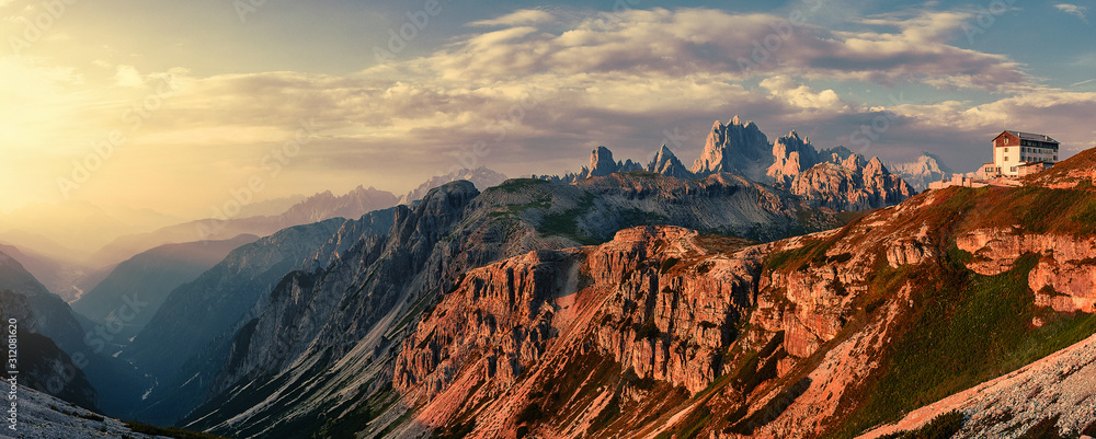 Wonderful Sunny Landscape of Dolomite Alps during sunrise. Panoramic view of famous Dolomites mountain peaks glowing in beautiful golden evening light at sunset in summer, South Tyrol, Italy.