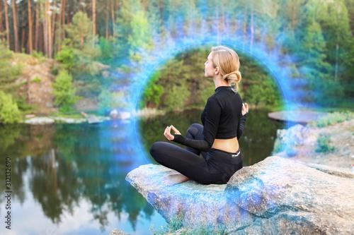 Beautiful young woman meditating near lake Fototapeta