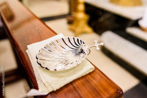 Slika na platnu Silver shell for holy water in Christian religious baptism.