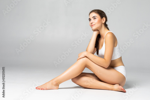 Photo Young beautiful woman in cotton underwear sitting on white background