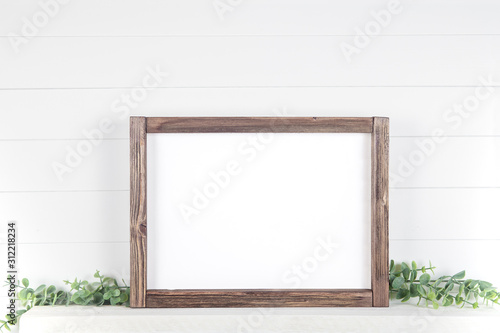 Stampa su Tela Mock up A4 horizontal frame made of rough wood with on a shelf with greens