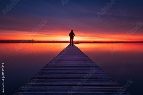 Fotografia, Obraz A man enjoying the colorful  dawn on a jetty in a lake