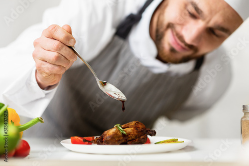 Photo Cook Man Pouring Sauce On Chicken Plating Dish In Kitchen