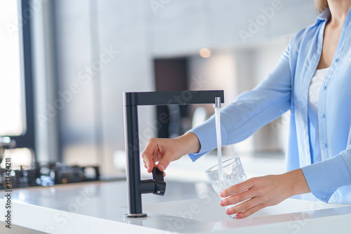 Fototapeta Woman pours fresh filtered purified water from a tap into a glass at kitchen at