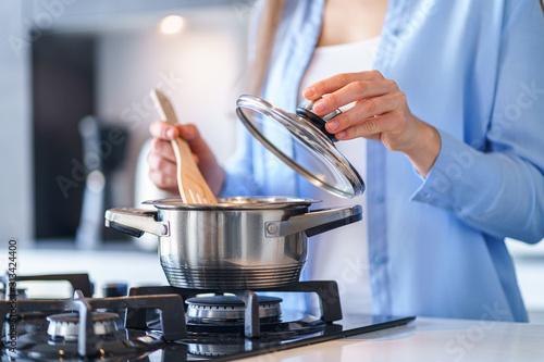 Fotografija Woman housewife using steel metallic saucepan for preparing dinner in the kitchen at home