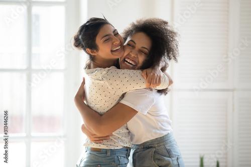 Happy multiethnic girlfriends have fun hugging indoors Fototapet