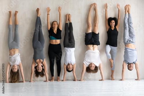 Tablou Canvas Happy diverse people doing handstand, fitness center staff portrait