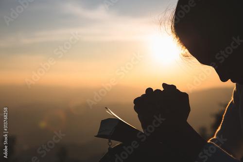 Fototapeta Woman praying in the morning on the sunrise background