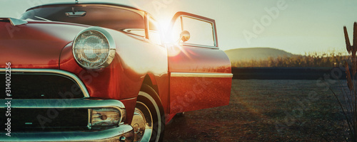 Fototapeta Czerwony klasyczny samochód na asfaltowej drodze podczas zmierzchu na wymiar