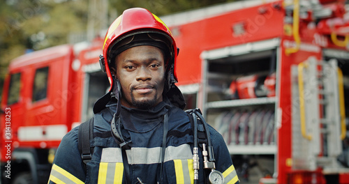 Photo Portrait of african american Firefighter in uniform and helmet near fire engine
