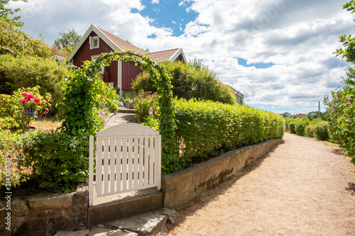 Slika na platnu Narrow gravel lane beside red and white traditional allotment cabin with picket fence and flowers
