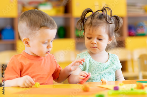 Toddlers boy and girl playing at table with educational toys Fototapeta