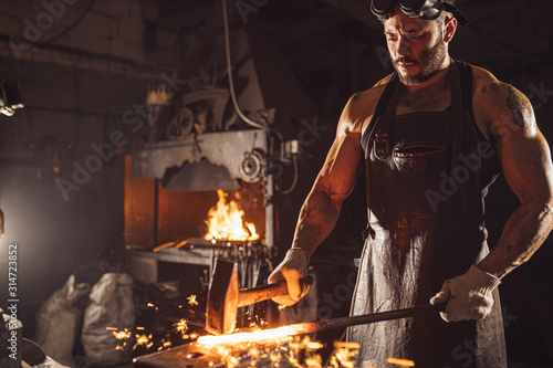 Canvas Print portrait of blacksmith in leather apron holding hot metal, wearing brown leather