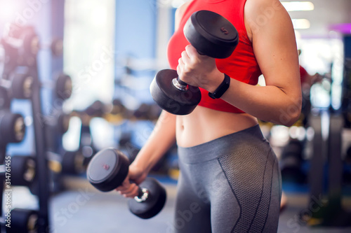Woman in red top training bicep with dumbbels in gym Fotobehang