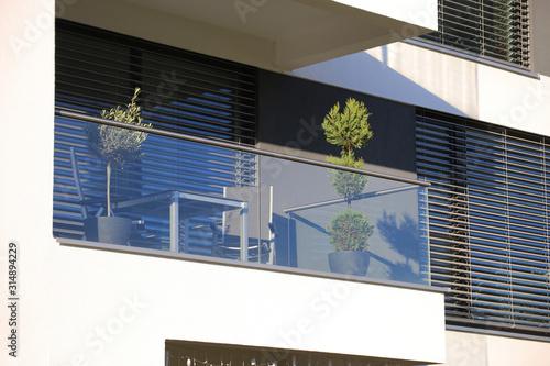 Fotografia Balkongeländer aus Glas und Edelstahl, dahinter Fenster mit modernen Jalousien
