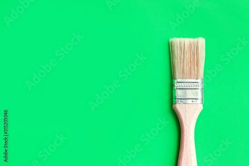 Fotografia Wooden handle paintbrush isolated on green
