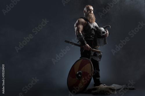 Fotografia, Obraz Medieval warrior berserk Viking with tattoo with axes attacks enemy