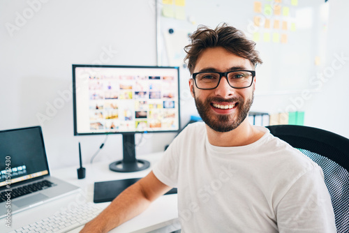Fototapeta Portrait of photographer sitting in office and smiling at camera with portfolio