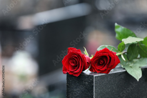 Valokuva Red roses on black granite tombstone outdoors, space for text