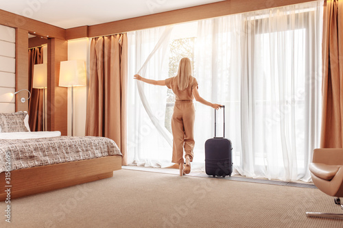 Successful joyful young beautiful well-groomed businesswoman in brown overalls with suitcase settled in luxury room and enjoys magnificent view from window Fototapet