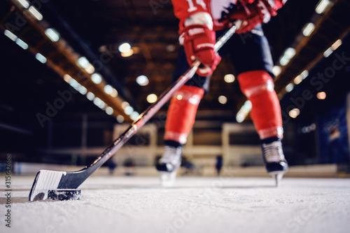 Zamyka up gracz w hokeja łyżwiarstwo z kijem i krążkiem hokojowym.