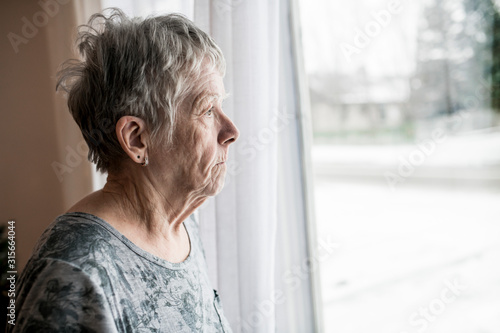 Obraz na plátně Sad senior woman at home close to window