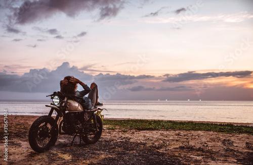 Canvas-taulu Beautiful girl having fun driving her custom cafe racer motorcycle, enjoying the
