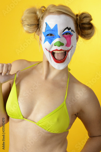Leinwand Poster Clown disguised as a horrorclown celebrates Halloween or carnival in bikini and