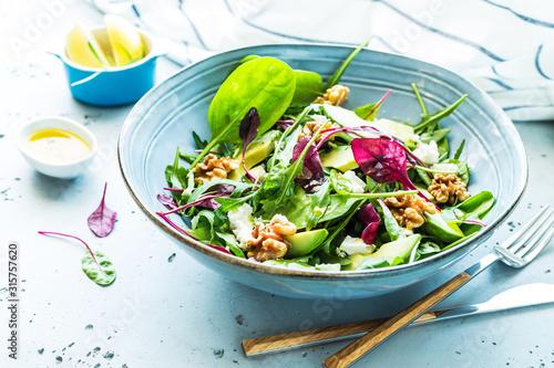 Photo Fresh colorful spring salad - avocado, walnuts and feta cheese