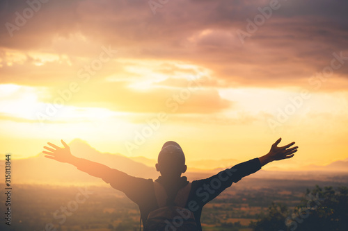 Платно Backpacker man raise hand up on top of mountain with sunset sky and clouds abstract background