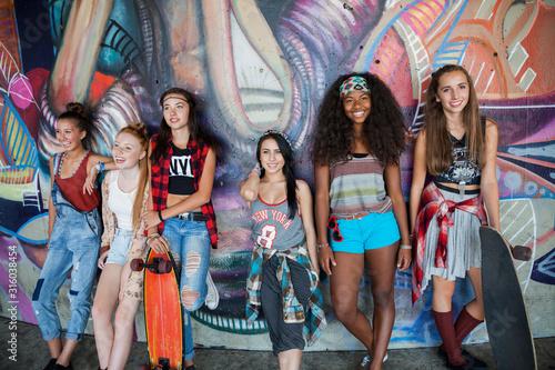 Foto mural Portrait of teenage girls leaning against graffiti wall