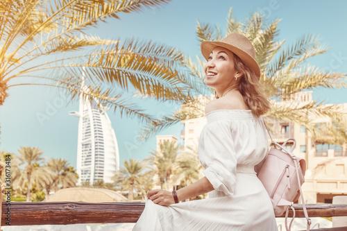 Cheerful Asian tourist girl with the famous Burj al Arab hotel building in Dubai Fototapeta