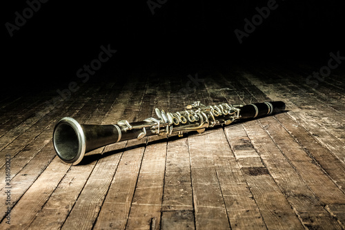 Tableau sur Toile black woodwind clarinet lies on a brown wooden stage