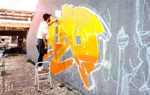 Street artist working on colored graffiti at public space wall - Modern art perform concept of urban guy painting live murales with yellow and orange aerosol color spray - Bright sunflare filter