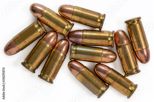 Photo Pile of 9mm bullets on a white background. Image